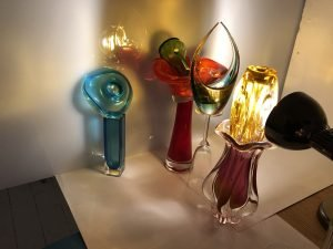 An arrangement of differently coloured glass objects with a light shining though onto a sheet of perspex.